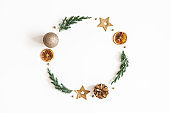 Christmas composition. Wreath made of fir tree branches, golden decorations on white background. Christmas, winter, new year concept. Flat lay, top view, copy space