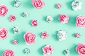 Flowers composition. Pattern made of rose flowers on mint background. Flat lay, top view