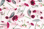 Flowers composition. Eucalyptus leaves and pink flowers on pastel pink background. Flat lay, top view