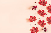 Autumn composition. Red maple leaves on beige background. Autumn, fall, thanksgiving day concept. Flat lay, top view, copy space