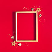 Christmas composition. Photo frame, golden and red decorations on red background. Christmas, winter, new year concept. Flat lay, top view, copy space