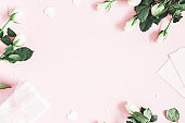 Valentine's Day composition. Gift box, white rose flowers, envelope on pastel pink background. Valentine's day, Mother's day concept. Flat lay, top view, copy space