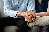 Close-up of Asian couple join hand give to encourage while sitting on the couch in the  room to consult mental health problems by doctor. Health and illness concepts