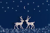 White Christmas reindeer on blue background with snow, stars and moon. Xmas greeting card with wishes. Flat lay.