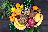 Ripe juicy tropical summer seasonal fruits on palm Leaf on wooden background. Vacation healthy lifestyle superfoods