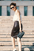 Fashionable brunette businesswoman in leather pencil skirt and sunglasses walking in the street, on stairs