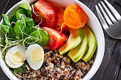 Fresh healthy salad with quinoa, cherry tomatoes and mixed greens, avocado, egg and micro greens on wood background top view. Food and health. Superfood meal. Clean eating. Healthy lifestyle