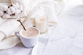 Bedding with a fluffy knitted plaid and cup of coffee, cotton flowers and candle. Cozy day. Flat lay, top view