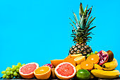 Summer background with fruit, tropical fresh fruits, juicy oranges, sliced mandarin, grapefruit and pineapple on blue background