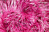 Abstract textured background of close up shiny pink Christmas tinsel