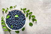 Fresh blueberry with leaves. Forest blue berry on plate, organic food and healthy superfood concept