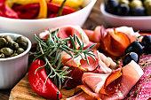 Traditional spanish tapa jamon serrano, or italian antipasto prosciutto, raw ham sliced on wooden board