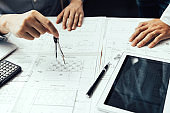 Two engineering working together and using digital tablet looking blueprint and analysis with architectural plan on desk.