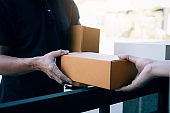 Close up of hands cargo staff are delivering cardboard boxes with parcels inside to the recipient's hand.