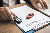Car salespeople are holding car keys by submitting to new car buyers with car insurance concept.