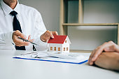 Salesman house brokers provide key to new homeowners in office.
