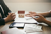 Customers buying houses are negotiating about the cost of home insurance with agents.