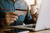 Men's hands are holding smart phones and drinking coffee with shopping online concept.