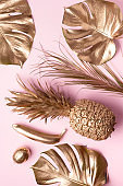 Golden exotic fruits, tropical palm, monstera leaves on pink background. Top view. Flat lay. Food concept. Creative layout of gold pineapple, banana, lemon with copy space.