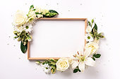 Floral frame of white flowers, green leaves on light paper background. Flat lay, top view. Spring and summer concept