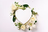 Frame of white flowers, paper heart over light background. Valentines day, Woman day concept. Spring or summer banner with copy space