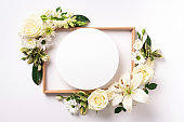 White roses, lily, gerbera and circle shape paper over light background. Flat lay, top view. Creative layout. Spring or summer banner with copy space. Flowers composition.