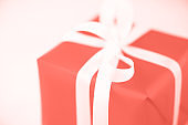 Gift box on trendy coral color background, copy space. Christmas, new year, birthday party, valentine's day, mother's and woman day concept. Present with love. Banner