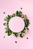 Creative layout made of green tropical leaves and white flowers on pink background. Top view. Flat lay. Summer or spring nature concept. Blank for advertising card or invitation. Mock up