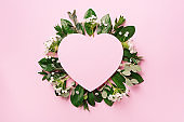 Tropical nature background with green leaves, white flowers and pink heart shaped paper for copy space. Top view. Flat lay. Creative advertising. Summer and love concept.