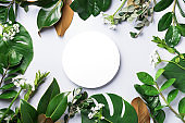Summer and spring concept. Tropical nature background with green leaves and white empty circle frame for copy space. Top view. Flat lay. Creative advertising