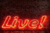 Illuminated Live text against brick wall at night