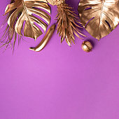 Golden exotic fruits, tropical palm, monstera leaves on violet background. Top view. Flat lay. Food concept. Creative layout of gold pineapple, banana, lemon with copy space.