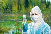 ecologist and dangerous dead water from a forest lake in a flask