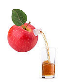 Red apple with leaf, juice pouring into a glass