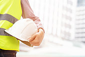 Close up front view of engineering male construction worker holding safety white helmet and wear reflective clothing for the safety of the work operation. outdoor of building background.