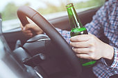 close up hand Drunk young man while driving a car with a bottle of beer. Don't drink and drive concept. Driving while intoxicated the danger may be a death.
