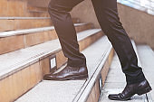 Close up legs shoes of young business man One person walking stepping going up the stairs in modern city, go up, success, grow up. with filter Tones retro vintage warm effect. stairway