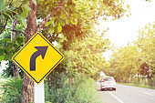 traffic sign placed beside along the road on route twisty winding slope. background driver car reduce speed and use a lower gear on country road.