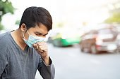 Portrait of man wearing facial hygienic mask nose outdoors. Ecology, air pollution car, Environmental and virus protection concept flu health against toxic dust covered the city of a health effect.