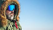portrait of winter adventurer over sky and snow