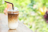 iced coffee latte with milk in plastic cup on wooden table