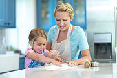 Mother and daughter rolling dough together