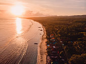 Sandy beach, local village and ocean in Nusa Penida with sunrise light. Aerial view