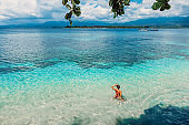 Young bikini woman relax in blue ocean on tropical island