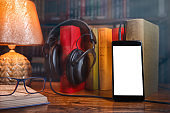 On a wooden table next to the lamp are headphones, a phone, a stack of books and glasses. The concept of modern technology and audiobooks. Mock up
