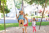 An elementary-age girl swings high at the park on a beautiful summer day!
