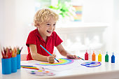 Kids paint. Child painting. Little boy drawing.