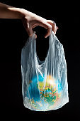 Close up of man hold in plastic bag Earth world globe isolated on black background.