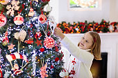 Child decorating Christmas tree. Kid on Xmas eve.
