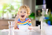 Child eating breakfast. Kid with milk and cereal.
